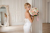 Beautiful blonde bride in the elegant white dress holding a wedding bouquet