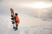 Rear view of professional snowboarder standing on the mountain peak with a board