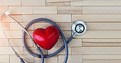 Medical concept, red heart and stethoscope on wooden background. The symbolic equipment for specialized doctor in cardiovascular desease.