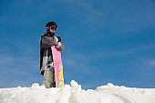 girl in ski goggles and ski equipment stands in the snow against the blue sky