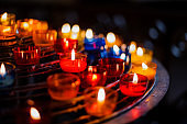 Burning candles in colorful candlesticks in a church