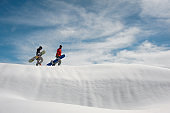 Two young snowboarders walking up the hill with the snowboards