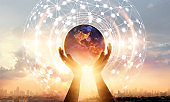 Abstract science. Hands touching earth and circle global network connection, data exchanges worldwide on city sunset background. Innovation. Creative and inspiration. Idea and imagination. Networking and technology concept. Elements of this image furnishe