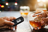 Hand holding alcoholic drink, another hold car remote, Drunk driving concept.