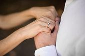 Bridegroom in white shirt holding brides hands