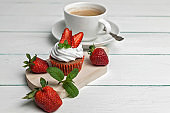 Vanilla cupcakes with strawberry and cup of coffee on a light wooden background