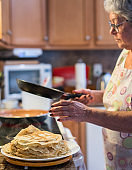 Active grandmother, silver haired 70-years-old senior woman, cooking pancakes in the domestic kitchen for breakfast.