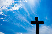 Silhouette of wooden cross with a bright blue sky and sun