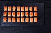 Sushi rolls set with salmon set on black slate, flat lay, free s