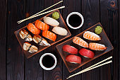 Delicious appetizing nigiri sushi set, served on clay plates wit