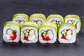 Delicious sushi rolls with smoked eel and caviar, wrapped in avocado slices. Restaurant food, japanese food art