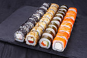 Delicious multicolored uramaki sushi rolls set, great assortment of tasty snacks, decorated with sesame. Restaurant menu, Japanese food art