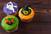 Tasty homemade Halloween cupcakes with decorations made of confe