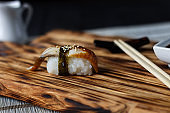 Delicious fresh nigiri with smoked eel served on wooden rustic t