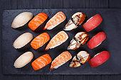 Nigiri sushi set on black stone slate, flat lay. Delicious tradi