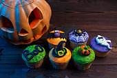 Tasty Halloween cupcakes set with colorful decorations: pumpkin,