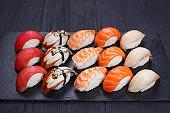 Traditional Japanese nigiri sushi set on black stone slate. Deli