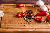 Mixed peppers in a wooden spoon, garlic and chili peppers. Spice