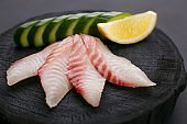 Red sea bream sashimi with cucumber and lemon slices on dark woo