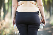 Overweight fat woman with measuring tape and slimming pills, vie