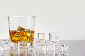 whiskey with ice cubes on white background