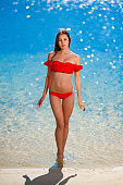 beautiful young woman in red bikini on blue water background