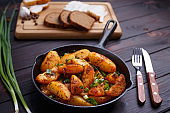 Roasted potatoes, bacon, rye bread and scallion on dark wooden t