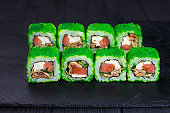 Tasty appetizing uramaki sushi roll with salmon and eel, covered