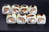 Tasty fresh maki sushi roll with eel and unagi sauce, covered wi