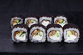 Tasty appetizing uramaki sushi roll with smoked eel, covered wit