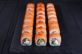Delicious california sushi rolls set on black slate, restaurant
