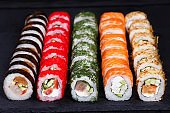 Bright colorful japanese sushi set, maki rolls served on black s