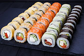 Colorful delicious set of sushi served on  black slate, close up