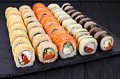 Delicious fresh multicolored sushi set on black slate, close-up.