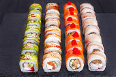 Delicious multicolored uramaki sushi rolls set, great assortment of tasty snacks with unagi sauce and sesame, decorated with caviar. Restaurant menu, Japanese food art