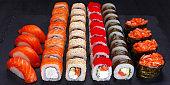 Appetizing maki and nigiri sushi set, served on black stone slate. Restaurant menu, Japanese food art.