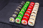 Delicious fresh multicolored sushi set on black slate, close-up. Traditional japanese food, restaurant serving