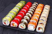 Tasty delicious multicolored appetizing sushi rolls set served o