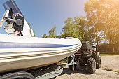 Transportation of inflatable boat on trailer. ATV quadbike moves ship to lake or river shore for launching. Beginning of water navigation and fishing season