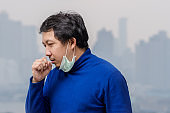 Asian man wearing the face mask against air pollution with coughing at the balcony of High Apartment which can see pollution and heavy fog over the bangkok cityscape background, healthcare concept