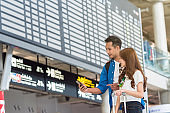Asian couple traveler using the smart mobile phone for check-in at the flight information screen in moddern an airport, travel and transportation with technology concept.