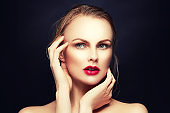 Beauty girl face with red lips make-up, green eyes touching clean skin with hands over black background