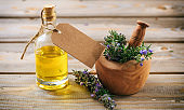 Rosemary essential oil and fresh blooming twig in a mortar, wooden table, blank tag, copy space