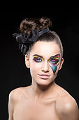 Girl with paint art on face as comics star over black background