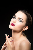 Portrait of young girl with bright glossy lips make-up, smoky eye shadows over dark background