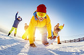 Funny friends in playful poses ski snowboarders
