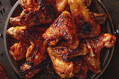 Barbecued chicken wings with bbq sauce on the plate top view.