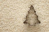 Christmas tree symbol on white polished rice background.