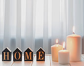 Burning candles and word home arranged from wooden letters.