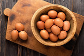 Yellow chicken eggs in a wooden bowl on a wooden background, top view